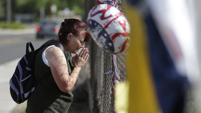 Deborah Heinemann pays her respects at a makeshift memorial outside the Granite Mountain Interagency Hotshot Crew fire station, Tuesday, July 2, 2013 in Prescott, Az., in Prescott, Ariz., honoring 19 firefighters killed battling a wildfire near Yarnell, Ariz., Sunday. The elite crew of firefighters were overtaken by the out-of-control blaze as they tried to protect themselves from the flames under fire-resistant shields. (AP Photo/Chris Carlson)