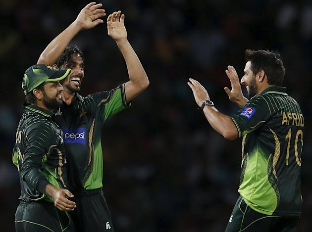 Pakistan's Ali celebrates with captain Afridi and Shehzad after taking the wicket of Sri Lanka's Perera during their first Twenty 20 cricket match in Colombo