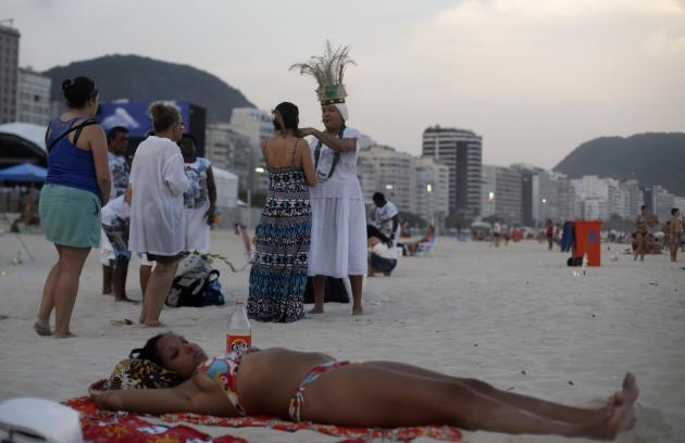 A woman relaxes on the beach as followers of Afro-Brazilian religion Umbanda attend a ceremony in tribute to Iemanja, goddess of the sea, in Copacabana Beach in Rio de Janeiro