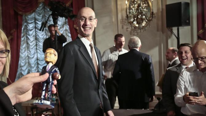 NBA Deputy Commissioner Adam Silver, left, reacts as a bobblehead doll of NBA Commissioner David Stern is shown off after a press conference after the NBA board of governors meeting, Wednesday, Oct. 23, 2013 in New York. Stern will formally step aside on Feb. 1, 2014, after 30 years and Silver will become the new league commissioner