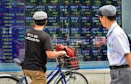 Pedestrians look at an electric quotation board flashing the Nikkei key index of the Tokyo Stock Exchange (TSE) on September 9, 2013. Japanese stocks jumped nearly three percent in opening trade on September 9 as investors cheered Tokyo winning its bid to host the 2020 Olympics.