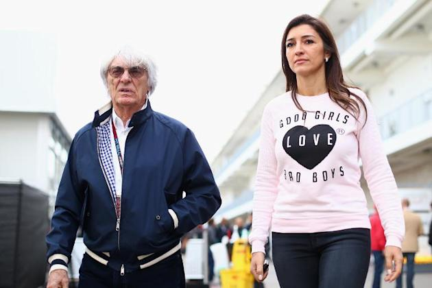 Formula One supremo Bernie Ecclestone and his wife Fabiana Flosi walk through the pits during the US F1 Grand Prix at the Circuit of The Americas in Austin, Texas, on November 14, 2013