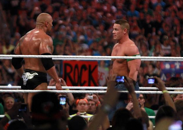 COMMERCIAL IMAGE - In this photograph taken by AP Images for WWE, Dwyane 'The Rock' Johnson, left, and John Cena face off at WrestleMania XXVIII in Sun Life Stadium on Sunday, April 1, 2012 in Miami.