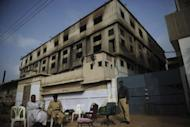 Pakistani security officials sit outside the burnt-out garment factory in Karachi. Three factory-owners facing murder charges over the deaths of 289 people in a huge fire in Karachi handed themselves in to court as Pakistan police described the moment the flames took hold