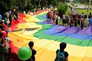 Supporters of lesbian, gay, bisexual, and transgender (LGBT) groups hold a huge rainbow banner as they march at the University of the Philippines (UP) campus in Manila in June 2012. The Philippines is is facing a HIV epidemic, with sex between men making up nearly 90 percent of all new cases, according to the health department and the United Nations' Development Programme (UNDP)