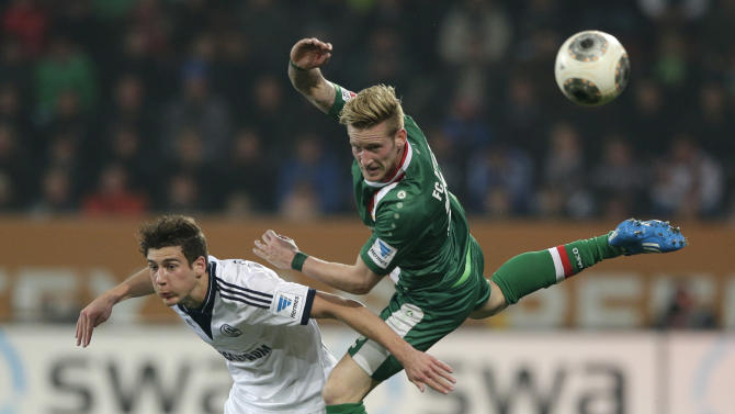 Schalke's Leon Goretzka, left, and Augsburg's Andre Hahn challenge for the ball during the German first division Bundesliga soccer match between FC Augsburg and FC Schalke 04, in Augsburg, southern Germany, Friday, March 14, 2014