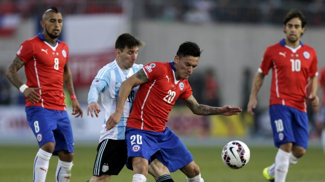 Chile's Aranguiz is tackled by Argentina's Messi as Chile's Vidal and Valdivia look on during their Copa America 2015 final soccer match at the National Stadium in Santiago