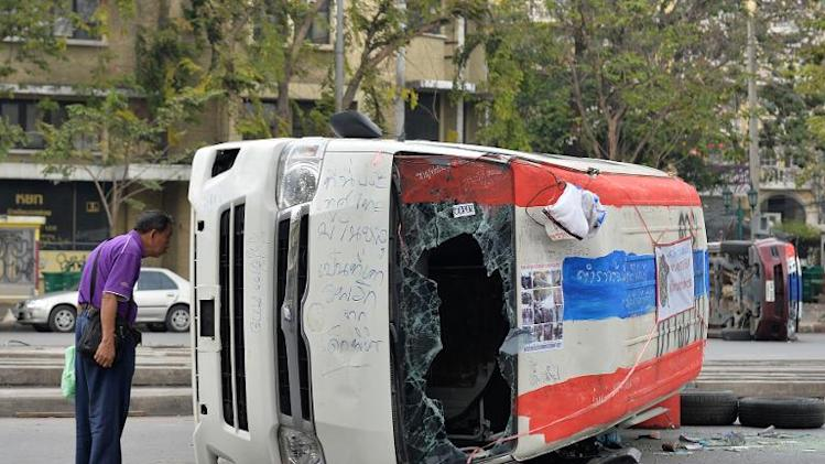 An upturned vehicle lies in the road in Bangkok on February 22, 2014 following anti-government riots