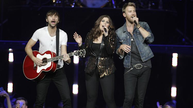 "FILE - This May 16, 2012 file photo shows, from left, Lady Antebellum's Charles Kelly,  Dave Haywood and Hillary Scott performing in Louisville, Ky. The platinum-selling trio plan to release a Christmas album, ""On This Winter's Night"" on Oct. 22. (AP Photo/Darron Cummings, file)"