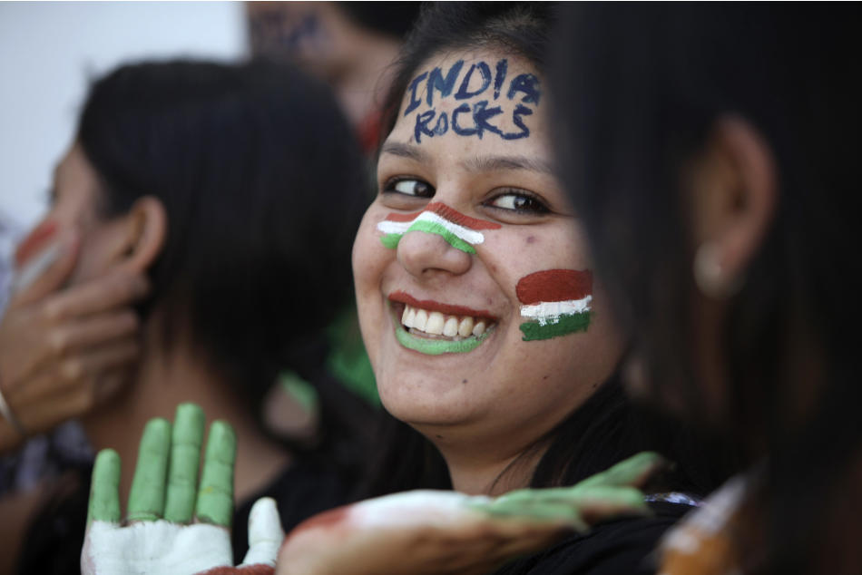 An Indian cricket fan, her face painted with the colors of the national flag, cheer for the team ahead of the ICC World Cup cricket final match between India and Sri Lanka, in Jammu, India, Friday, Ap