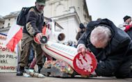 Two men prepare a sculpture depicting a crashed plane ahead of a ceremony marking the third anniversary of the crash in Smolensk, in front of the presidential palace in Warsaw on April 10, 2013. Poland's opposition leader laid flowers Wednesday in honour of twin and ex-president Lech Kaczynski, who died in a jet crash in Russia three years ago that one third of Poles believe was an assassination