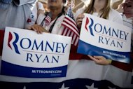"Supporters hold campaign signs as US Republican presidential candidate Mitt Romney and his running mate Paul Ryan speak at a campaign rally in Manassas, Virginia, on August 11. Romney and Ryan will try to energize supporters in North Carolina Sunday after they hit the road on a bus tour across must-win US states, selling themselves as the duo who can ""save the American dream."""