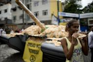 A girl eats bread next to a fake tank covered with bread on display to protest against the weapon market in the Santa Marta shantytown. After exhausting negotiations concluding on the eve of a global summit, UN members on Tuesday backed a plan for nursing Earth's sick environment back to health and tackling poverty through greener growth
