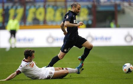 Inter Milan's Palacio fights for the ball with Torino's Darmian during their Italian Serie A soccer match in Milan