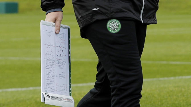 Celtic manager Brendan Rodgers holds a clipboard during training