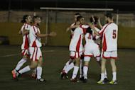In this photo dated Sunday, Feb. 5, 2017, players of Hope Refugee Football Club celebrate a goal during a soccer match in western Athens. Former Greek national soccer team goalkeeper Antonis Nikopolidis, who became a national hero in 2004 during the European Cup, is heading a project to help refugees stranded in Greece regain a sense of purpose, working as a team. On weekends they play in an amateur league against teams made up of professional groups like lawyers, telecom workers, and accountants. (AP Photo/Thanassis Stavrakis)