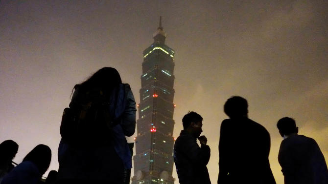 "Onlookers watch Taipei 101 building as it turns its lights off to observe international ""Earth Hour"" campaign, Saturday, March 23, 2013, in Taipei, Taiwan. Around 100 people gathered outside the skyscraper Saturday, using energy saving LED lights to observe the global event that encourages people to turn off their lights for 60 minutes. (AP Photo/Wally Santana)"
