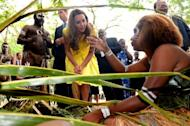 Britain's Prince William (2nd L) and his wife Catherine, the Duchess of Cambridge, speak with traditional weavers during a visit to a cultural village in Honiara on September 17, 2012. The royal couple are on a nine-day tour marking Queen Elizabeth II's Diamond Jubilee, and have already visited Singapore and Malaysia before arriving in the Solomon Islands