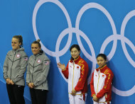 Gold medalists Wu Minxia, 2nd right, and He Zi, right, wave, as US Silver medalists Abigail Johnston, left, and Kelci Bryant, 2nd left, look on during the winning ceremony for the 3 Meter Synchronized Springboard final at the Aquatics Centre in the Olympic Park during the 2012 Summer Olympics in London, Sunday, July 29, 2012.(AP Photo/Lefteris Pitarakis)