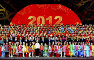 in this photo taken on Jan. 20, 2012 and released by China's Xinhua News Agency, senior Communist Party members pose for photos with performers and crew members of China Central Television's (CCTV's) Lunar New Year gala program during their rehearsal in Beijing. Chinese state broadcaster CCTV said Wednesday, Feb. 8, 2012, it is launching its American service this week as part of a major overseas expansion drive aimed at boosting China's international influence. (AP Photo/Xinhua, Zhang Duo) NO SALES