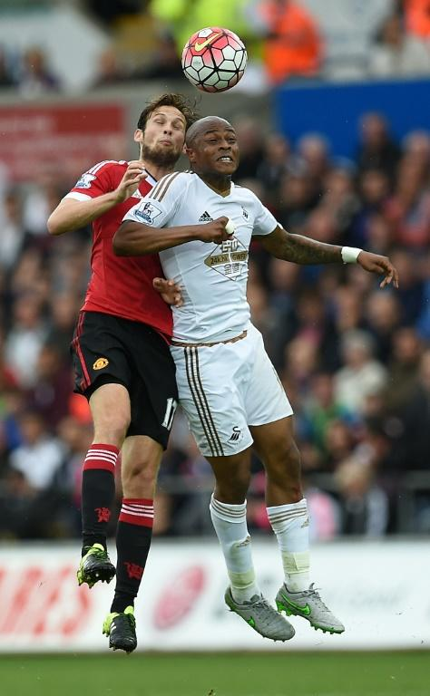 Manchester United's midfielder Daley Blind (L) jumps for the ball against Swansea City's striker Andre Ayew during an English Premier League football match at The Liberty Stadium in Swansea, s