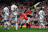 Manchester United's English midfielder Michael Carrick (2nd R) congratulates goal-scorer Paul Scholes during the English Premier League football match between Manchester United and Swansea City at Old Trafford in Manchester. Manchester United ensured the race for the Premier League title will go to the final game of the season as they beat Swansea City 2-0 at Old Trafford here on Sunday