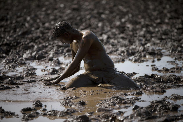 In this Friday, Feb. 27, 2015 photo, an Israeli high-school senior preparing to join the Israeli military later this year pauses in mud during an exercise at a privately run training camp for military