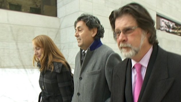 Father Joseph LeClair (centre) is seen leaving his sentencing in March. (CBC)