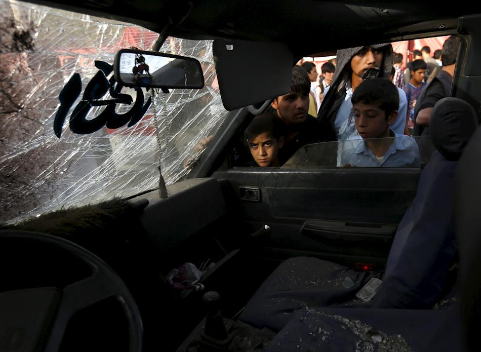 Afghan boys look inside a damaged car at the site of a car bomb in Kabul, Afghanistan