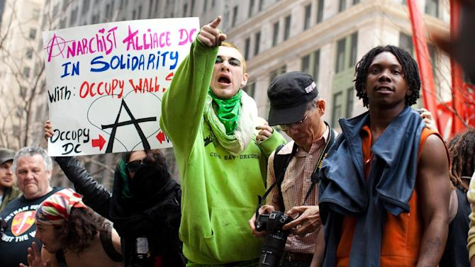 An Occupy Wall Street protestor yells at the police after arrests were made following a march to celebrate the protest's sixth month, Saturday, March 17, 2012, in New York.  With the city's attention focused on the huge St. Patrick's Day Parade many blocks uptown, the Occupy rally at Zuccotti Park on Saturday drew a far smaller crowd than the demonstrations seen in the city when the movement was at its peak in the fall. A couple hundred people attended. (AP Photo/John Minchillo)