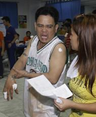 A Filipino man reacts following his treatment after sustaining injuries from firecrackers at New Year at Manila's Rizal Park, Philippines on Sunday Jan. 1, 2012. More than 200 people have been injured by illegal firecrackers and celebratory gunfire in the Philippines despite a government scare campaign against reckless New Year revelries, officials recently said. (AP Photo/Aaron Favila)