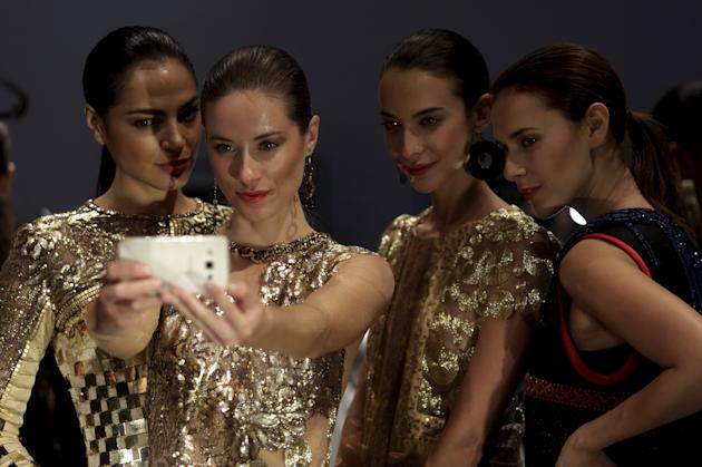 Models take a selfie backstage before the presentation of a collection by Peruvian designer Ani Alvarez Calderon at Municipal theater Lima