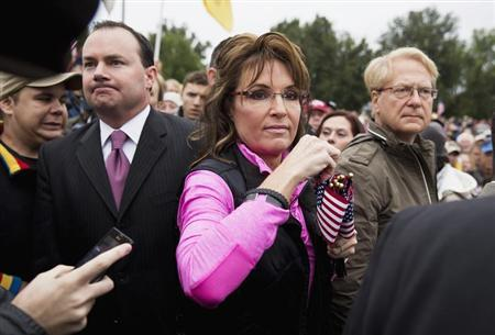 "Senator Mike Lee (L)(R-UT) watches as Former Alaska Governor Sarah Palin hands out American Flags to protesters during the ""Million Vet March on the Memorials"" at the U.S. National World War II Memorial in Washington October 13, 2013. REUTERS/Joshua Roberts"