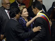 Brazilian President Dilma Rousseff (C) and Bolivian President Evo Morales (L) greet newly inaugurated Venezuelan President Nicolas Maduro in Caracas on April 19, 2013