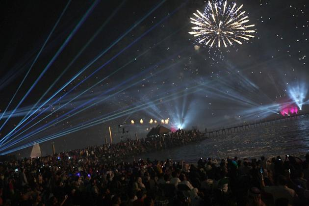People gather to watch fireworks as they light the sky near the Kuwait Towers during celebrations marking the Gulf state's 50th anniversary of its constitution, in Kuwait City on November 10, 2012.  K