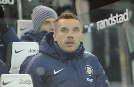 New Inter Milan's player Podolski sits on the bench before their Italian Serie A soccer match against Juventus at the Juventus stadium in Turin