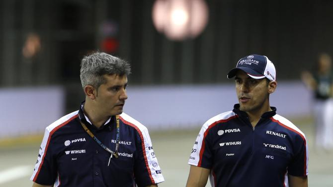 Williams F1 driver Maldonado walks the Marina Bay Street Circuit with a crew member ahead of the Singapore F1 Grand Prix