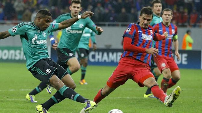 Schalke's Jefferson Farfan, left, takes a shot at goal next to Bucharest's Lukasz Szukala, during their Champions League Group E soccer match, at the National Arena in Bucharest, Romania, Tuesday, Nov. 26, 2013
