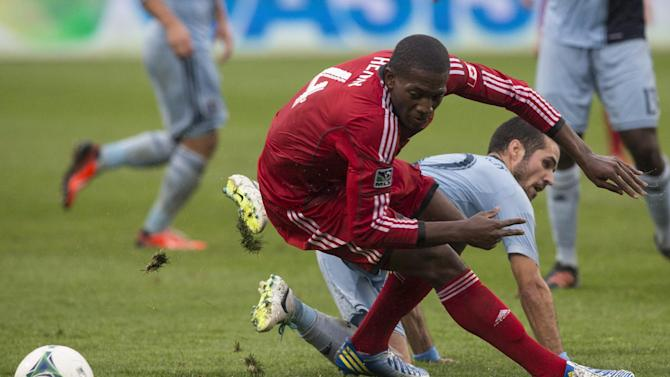 Toronto FC 's Doniel Henry, left, and Sporting Kansas City's Benny Felhaber battle for the ball  during the first half of an MLS soccer game in Toronto on Saturday, Sept, 21, 2013