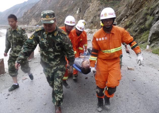Rescuers and paramilitary policemen carry an injured man with a stretcher after a 5.9 magnitude earthquake hit Deqen county
