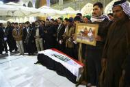 Mourners pray near the coffin of a soldier, who was killed during clashes in Falluja, during his funeral in Najaf, 160 km (99 miles) south of Baghdad, January 5, 2014. REUTERS/Ahmad Mousa