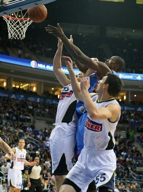 The NBA team Oklahoma City Thunder's Serge Ibaka, center, and Gasper Vidmar, left, and Emir Preldzic of  Fenerbahce Ulker fight for the ball during a basketball game in Istanbul, Turkey, Saturday, Oct. 5, 2-13. Oklahoma City Thunder has opened the preseason schedule with a game against the five-time Turkish champions at the Ulker Sports Arena. (AP Photo)