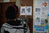 A woman looks at the obituary notices for medical staff who have died from the Ebola virus at the Kenema government hospital, in Sierra Leone, on August 16, 2014