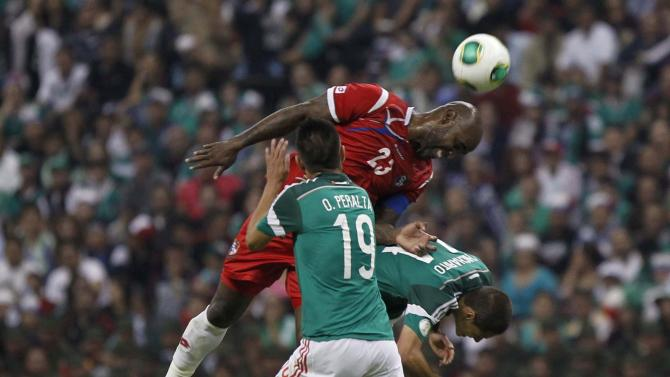 Panama's Felipe Baloy jumps for the ball with Mexico's Oribe Peralta and Javier Hernandez during their 2014 World Cup qualifying soccer match at Azteca stadium in Mexico City
