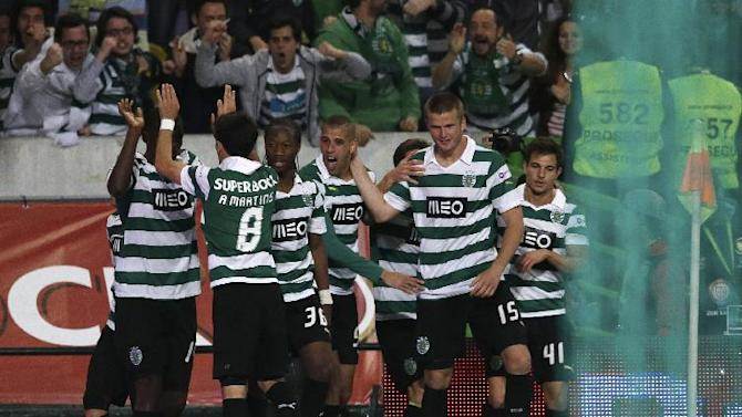 Sporting players celebrate after Slimani, from Algeria, center, scored the opening goal during their Portuguese league soccer match with Porto Sunday, March 16, 2014, at Sporting's Alvalade stadium in Lisbon