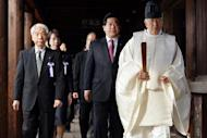 Japanese lawmakers follow a Shinto priest during a visit to the controversial Yasukuni shrine in Tokyo on October 18, 2013