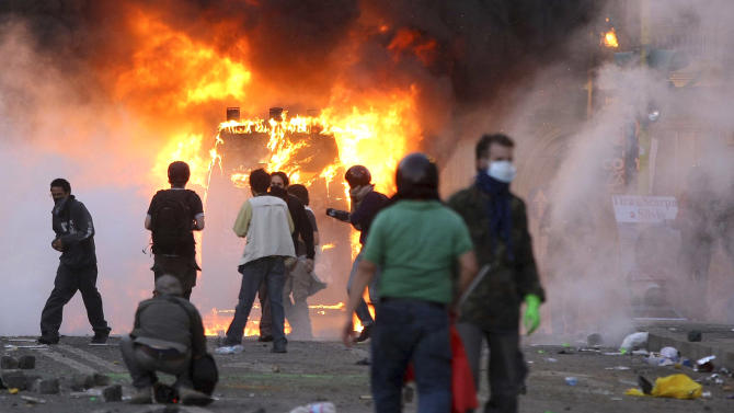 "A Carabinieri (Italian paramilitary police) van is engulfed in flames after protesters set it on fire during clashes in Rome, Saturday, Oct. 15, 2011. Italian police fired tear gas and water cannons as protesters in Rome turned a demonstration against corporate greed into a riot Saturday, smashing shop and bank windows, torching cars and hurling bottles. The protest in the Italian capital was part of ""Occupy Wall Street"" demonstrations against capitalism and austerity measures that went global Saturday, leading to dozens of marches and protests worldwide. (AP Photo/Roberto Monaldo, Lapresse)   Italy Out"