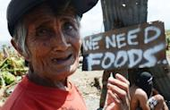 An elderly woman begs for alms in the town of Nabunturan town in Compostela Valley province on Sunday. When a truck from a local power company arrived in one town to distribute relief supplies, it was mobbed by hungry villagers and many children were almost trampled in the chaos