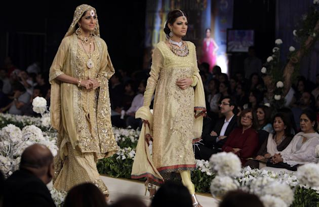 Models present creations of Pakistani designer Moona Imran during a show of the Bridal Couture Week in Lahore, Pakistan late night on Saturday, Oct. 15, 2011. (AP Photo/K.M. Chaudary)