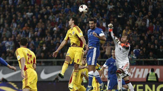 Greece's Alexandros Tziolis jumps between Romania's Ciprian Marica and goalkeeper Bogdan Lobont during their 2014 World Cup qualifying playoff first leg soccer match at Karaiskaki stadium in Piraeus